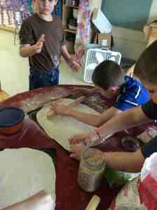 boys rolling out pizza dough